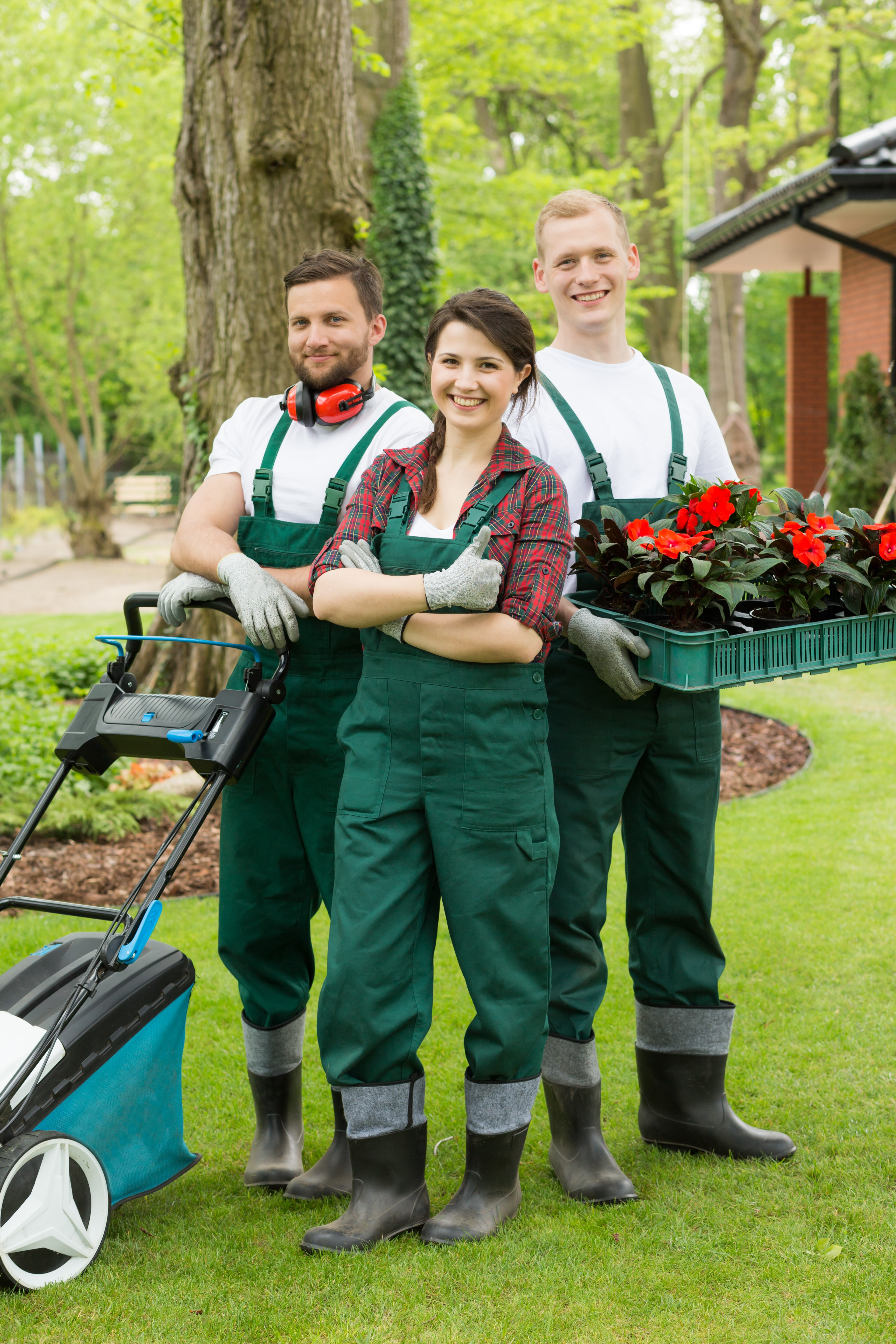 Happy gardeners with the box full of flower plants and the lawn mower in the garden